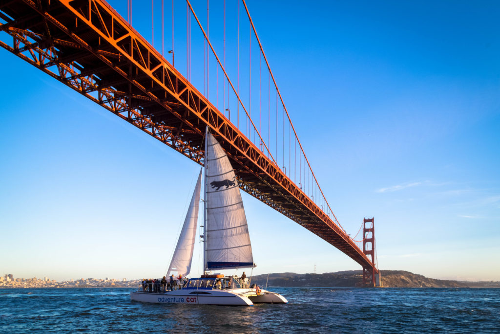 Adventure Cat sailing under the Golden Gate bridge with the city in the background