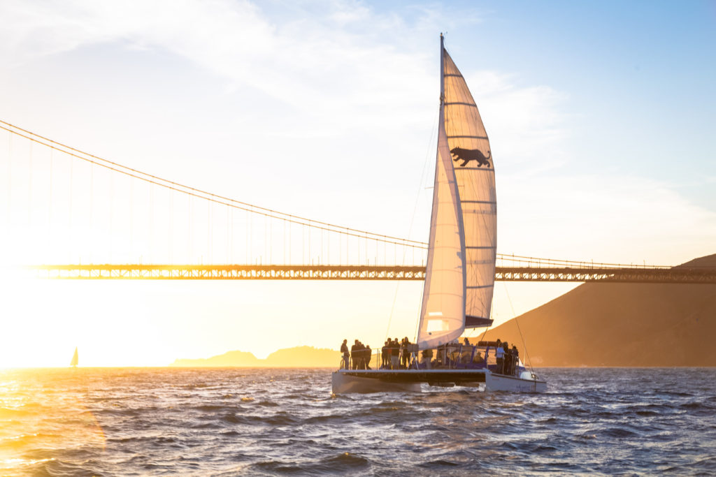 Adventure Cat sailing in front of the Golden Gate bridge just before sunset