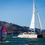 Adventure Cat sailing next to a wind surfer on the San Francisco Bay