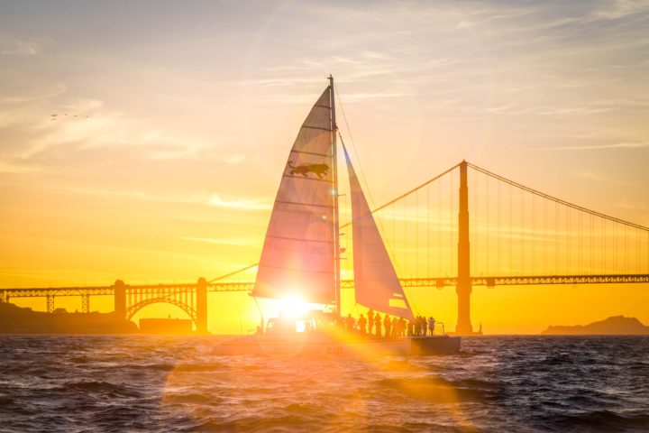 Adventure Cat sailing parallel to the Golden Gate Bridge just as the sun sets