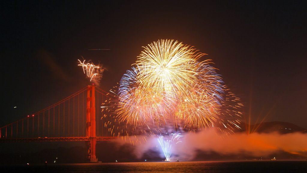 fireworks exploding over the Golden Gate bridge on 4th of July