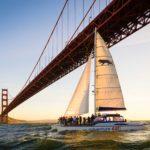 Adventure Cat sailing under the Golden Gate bridge at sunset